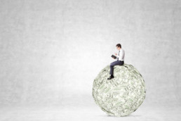 Man sitting on large ball of money